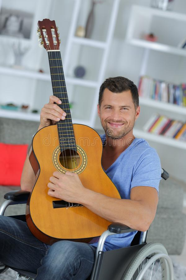 Musicien dévoué handicapé heureux jouant la guitare photographie stock libre de droits