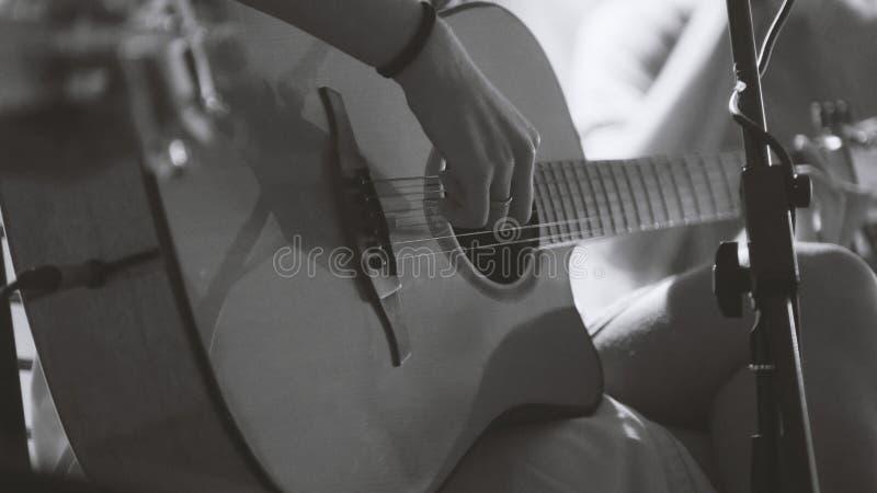 Musicien dans la boîte de nuit - guitariste joue la guitare acoustique de bleus, extrêmement fin - noire et blanche photos stock