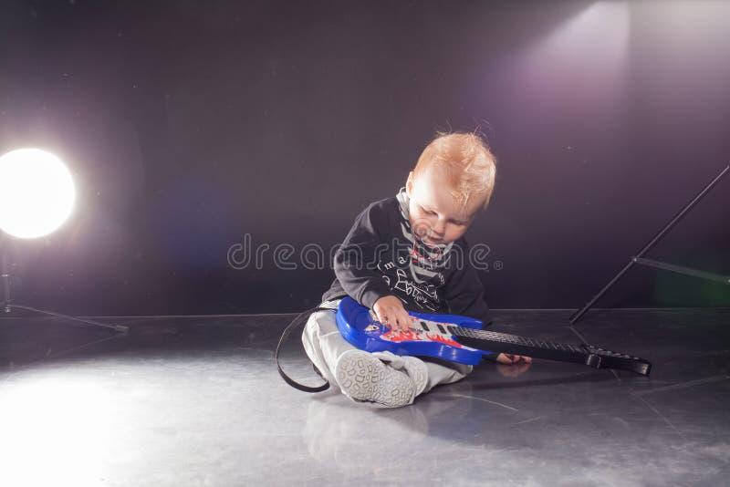 Musicien de petit garçon jouant la musique rock sur la guitare image stock