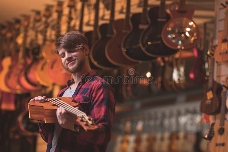 Musicien de sourire avec une ukulélé à l'intérieur photographie stock