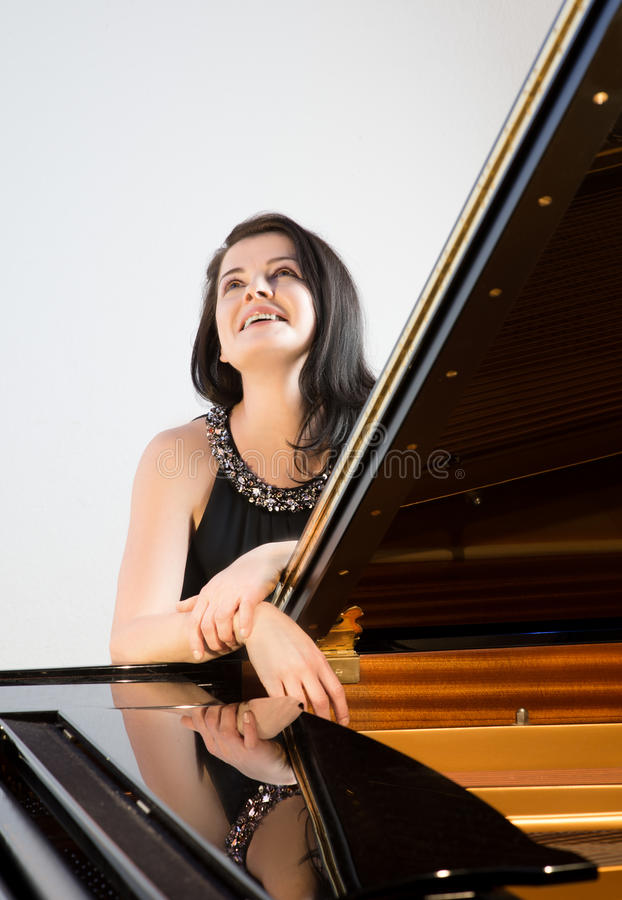Musicien de sourire par le grand piano photos stock