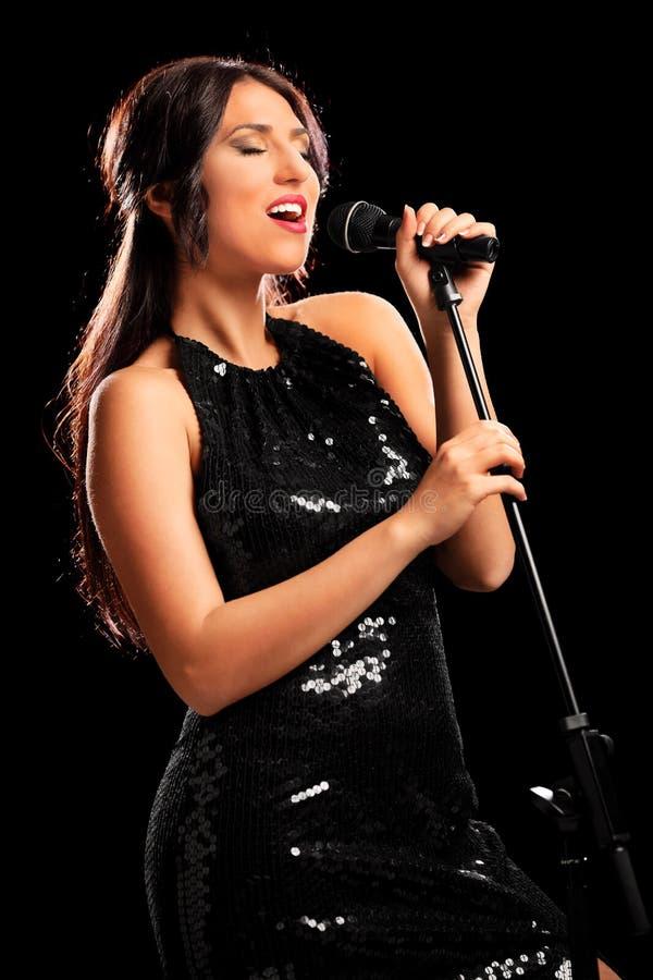 Musicien féminin chantant sur un microphone photographie stock libre de droits
