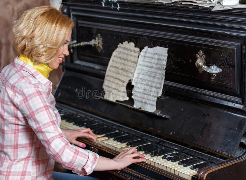 Musicien féminin de sourire jouant la musique de feuille sur le rétro piano photographie stock libre de droits