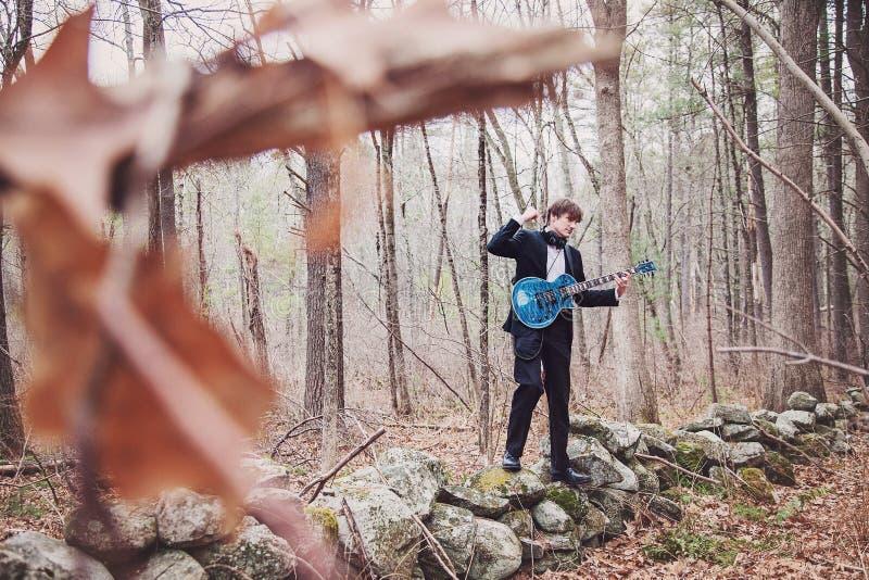 Musicien jouant de la guitare dans les bois images stock