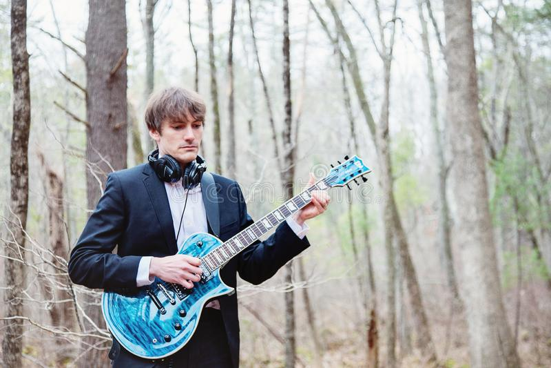 Musicien jouant de la guitare dans les bois images libres de droits