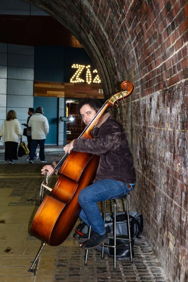 Musicien jouant la basse dans la ville de Londres de Southwark, sur la rive sud de la Tamise près du théâtre Londres de globe image libre de droits