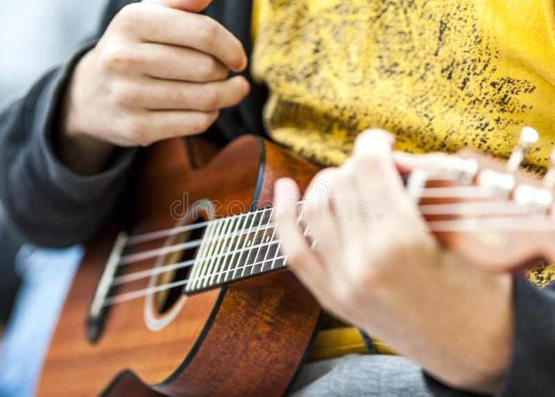 Musicien jouant la guitare acoustique ? une r?union intime photographie stock