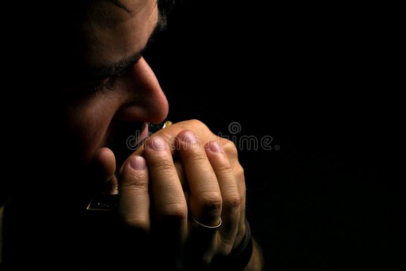 Musicien jouant sur l'harmonica photo stock