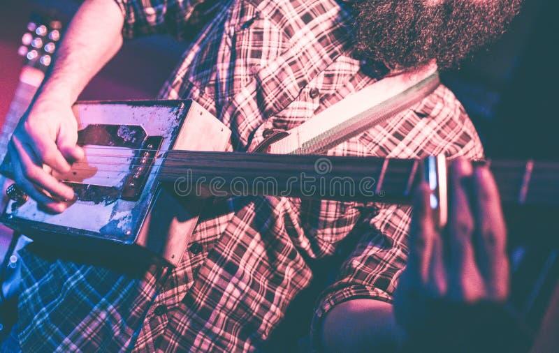Musicien jouant une guitare étrange photos libres de droits