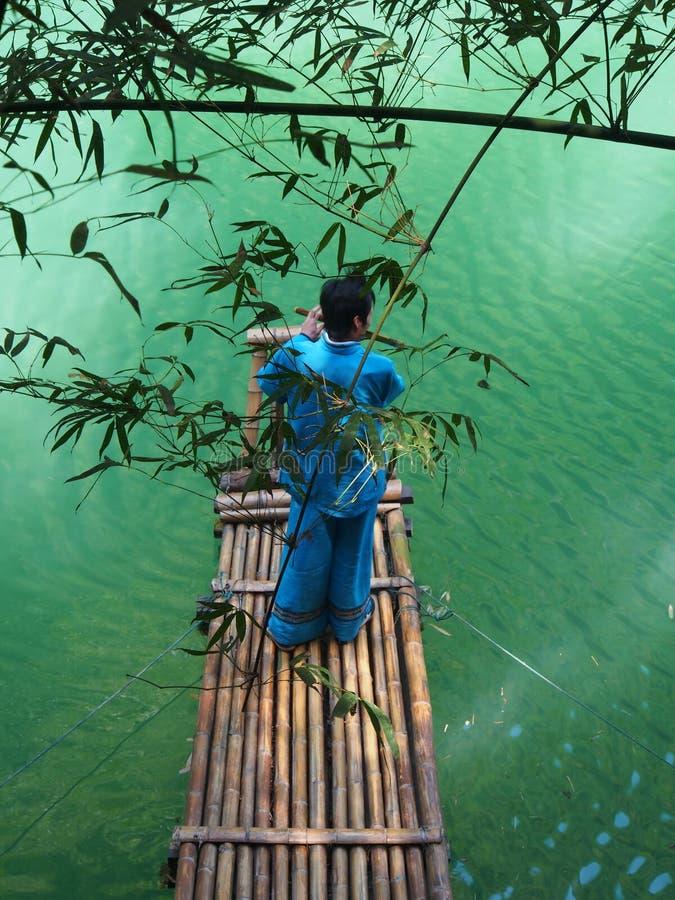 Musicien local de Chinois avec l'arbre en bambou et la rivière à l'emplacement image stock