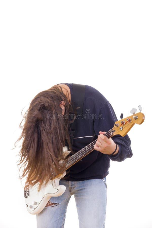 Musicien masculin jouant la guitare basse avec des cheveux vers le bas image libre de droits