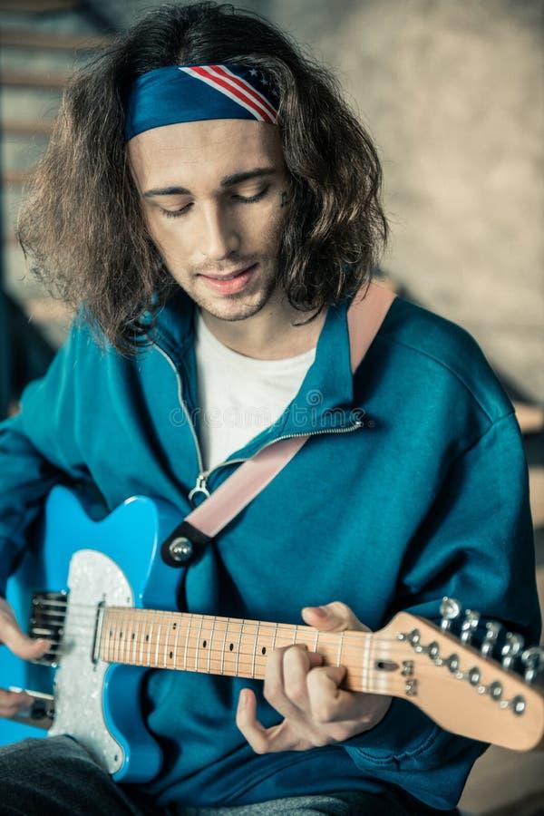 Musicien qualifié aux cheveux longs avec la chaume noire chantant et jouant en même temps photos libres de droits