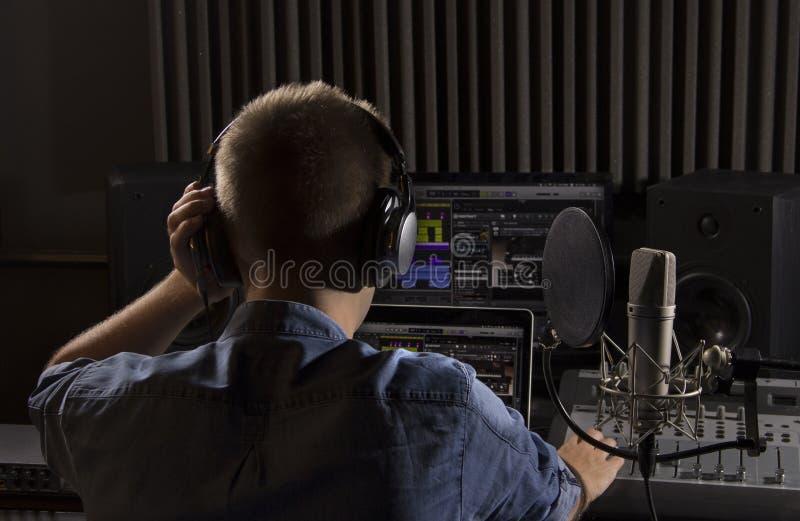 Musicien travaillant et produisant la musique dans son studio sain moderne image stock
