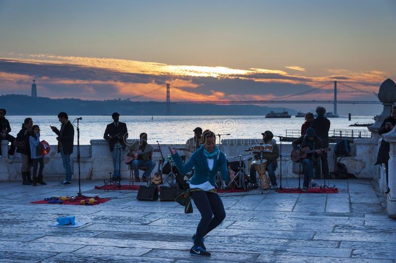 Musiciens de rue jouant chez le Cais DAS Colunas dans la ville de Lisbonne avec le Tage et les 25 d'April Bridge sur le dos photo stock