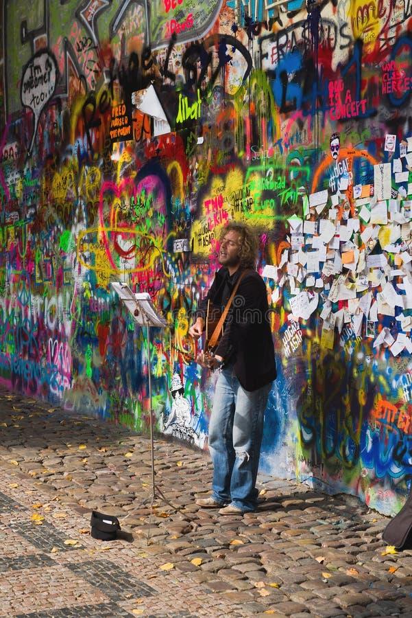 Musicista ambulante della via che esegue davanti a John Lennon Graffiti Wall fotografie stock