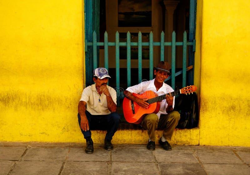Musicista ambulante e un uomo qualunque di Trinidad, Cuba sulla notte di Natale 2013 fotografie stock
