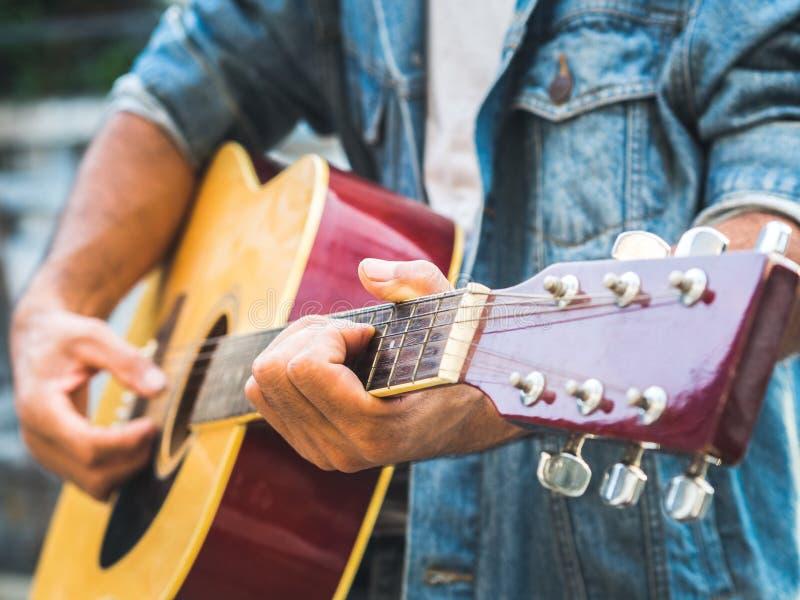 Musicista bello che gioca chitarra acustica sul fondo della sfuocatura wo fotografia stock