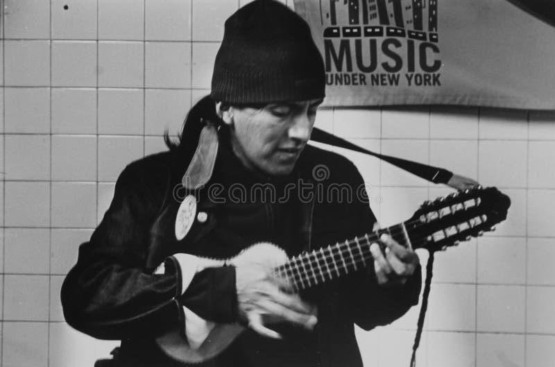 Musicista che gioca la chitarra dentro il sottopassaggio in Jackson Heights fotografia stock