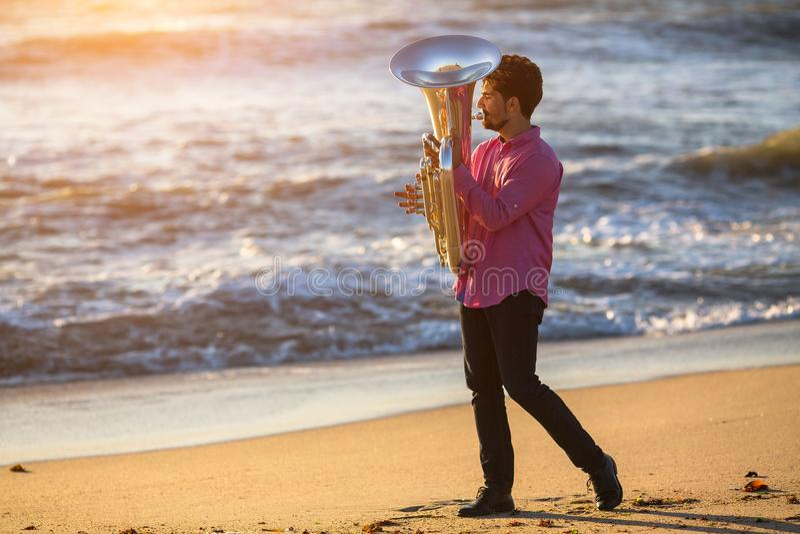 Musicista che gioca la tuba dello strumento musicale sulla spiaggia del mare concerto fotografie stock