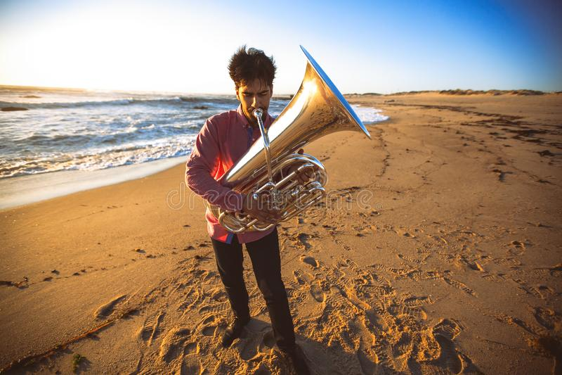 Musicista che gioca la tuba sull'hobby della costa dell'oceano fotografia stock