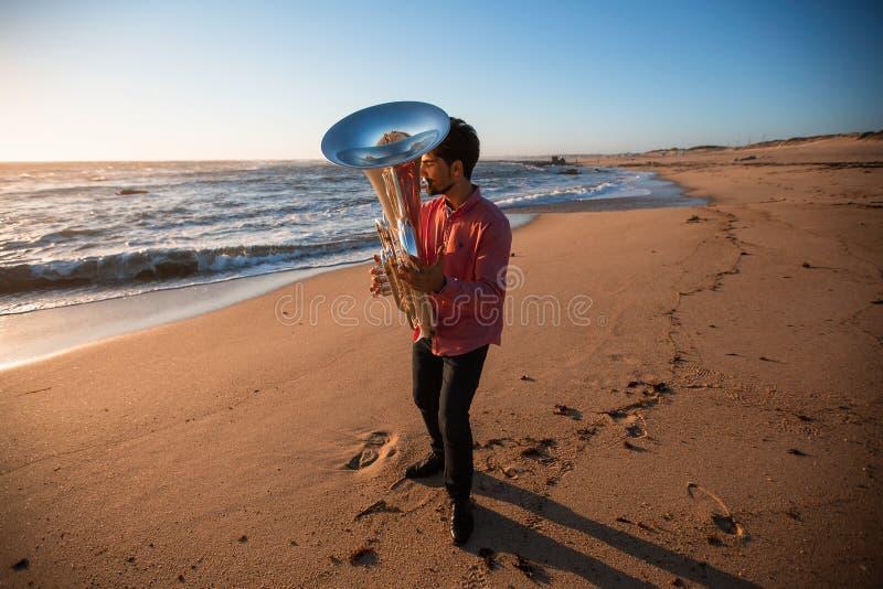 Musicista che gioca la tuba sull'hobby della costa di mare immagine stock libera da diritti