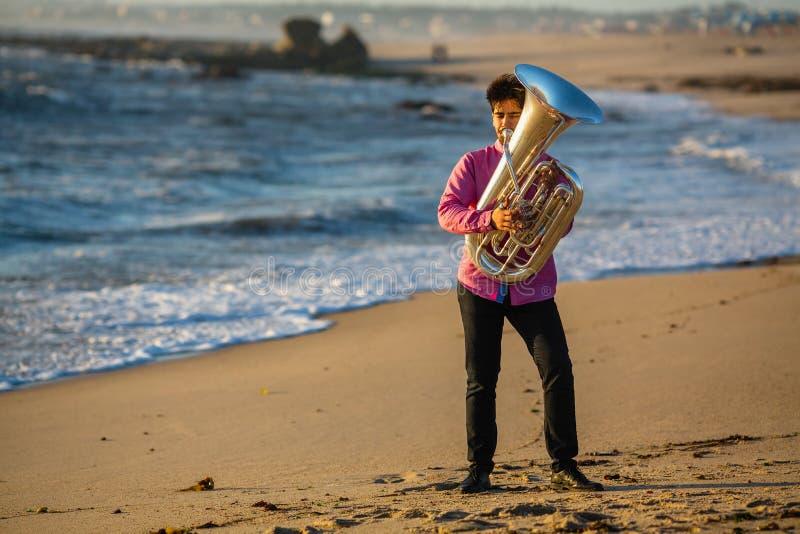 Musicista che gioca la tuba sull'hobby della costa di mare fotografia stock libera da diritti