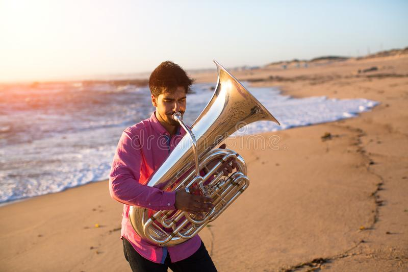 Musicista che gioca la tuba sull'hobby della costa di mare fotografia stock