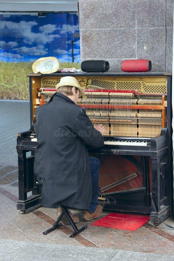 Musicista che gioca piano all'aperto Vita dei guadagni del pianista giocando con il piano immagine stock libera da diritti
