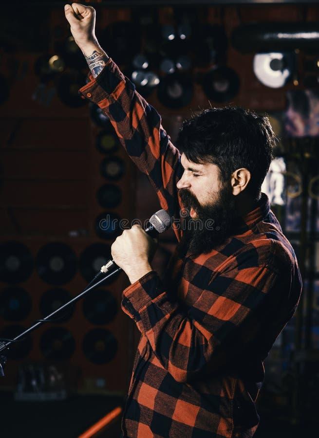 Musicista con la canzone di canto dei baffi e della barba nel karaoke I pantaloni a vita bassa gradiscono cantare in scena Uomo c fotografia stock