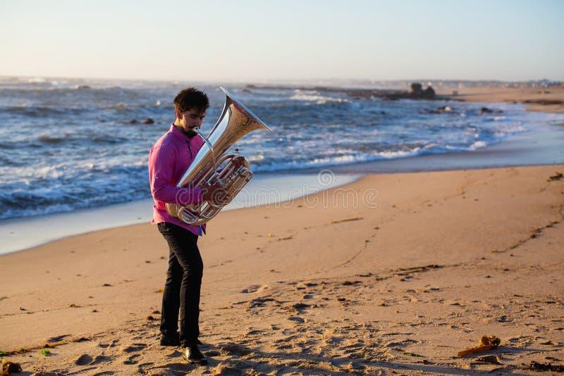 Musicista con una tuba che gioca sulla spiaggia del mare hobby fotografia stock