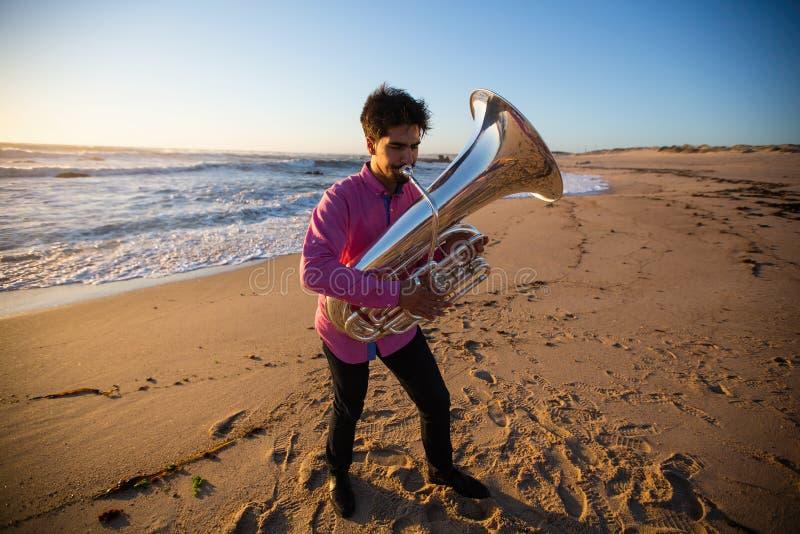 Musicista con una tuba che gioca sulla spiaggia del mare hobby fotografie stock libere da diritti