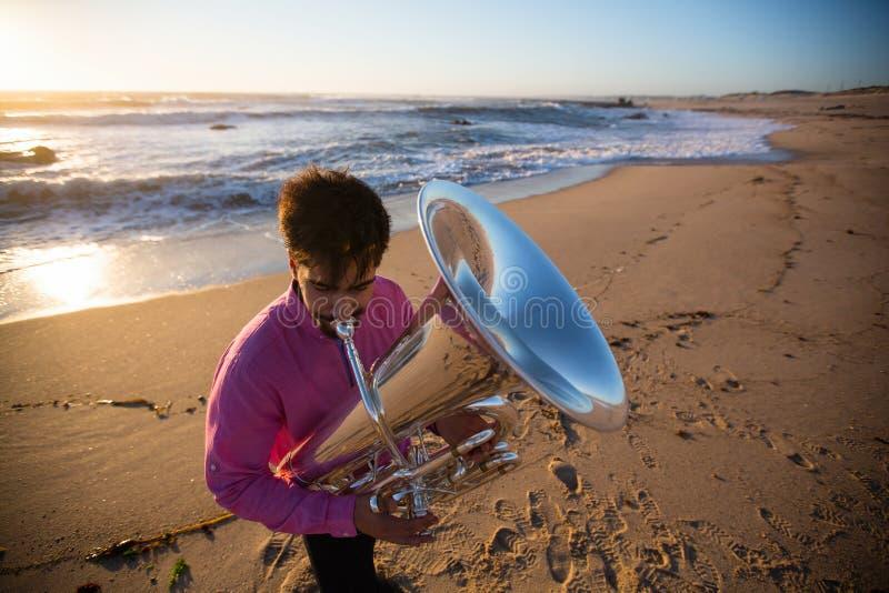 Musicista con una tuba che gioca sulla spiaggia del mare jazz fotografia stock