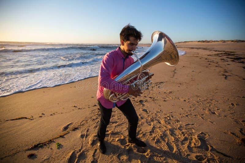 Musicista con una tuba che gioca sulla spiaggia dell'oceano hobby immagine stock