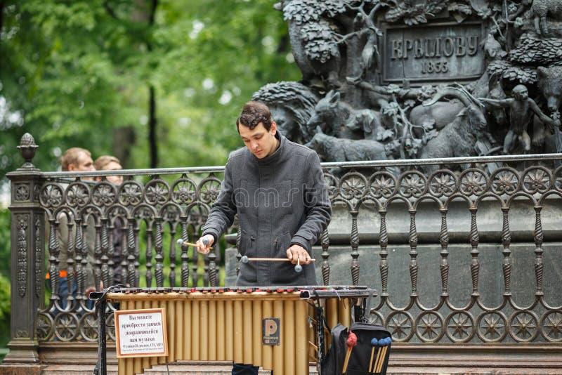 Musicista della via che gioca il metallophone cromatico dei campanelli vicino al monumento a Krylov St Petersburg, Russia fotografia stock libera da diritti