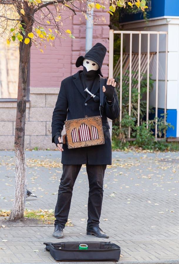 Musicista della via in una maschera e vestiti neri con un vecchio organo a rullo che elemosinano sulle vie immagini stock libere da diritti