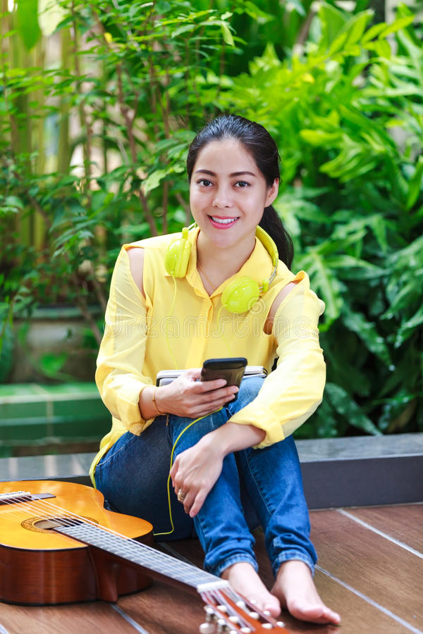 Musicista femminile asiatico che per mezzo del telefono cellulare con le cuffie per il ente fotografia stock libera da diritti