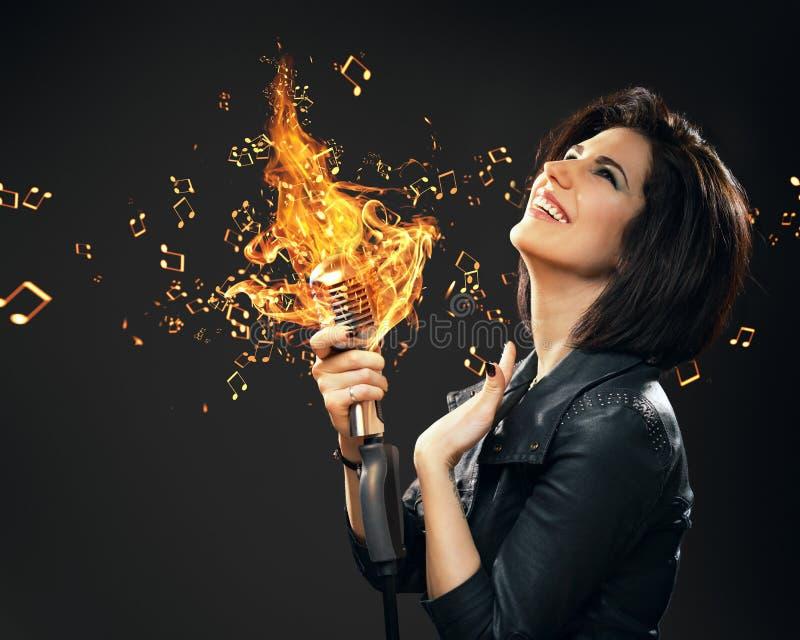 Musicista femminile della roccia che passa mic bruciante immagini stock