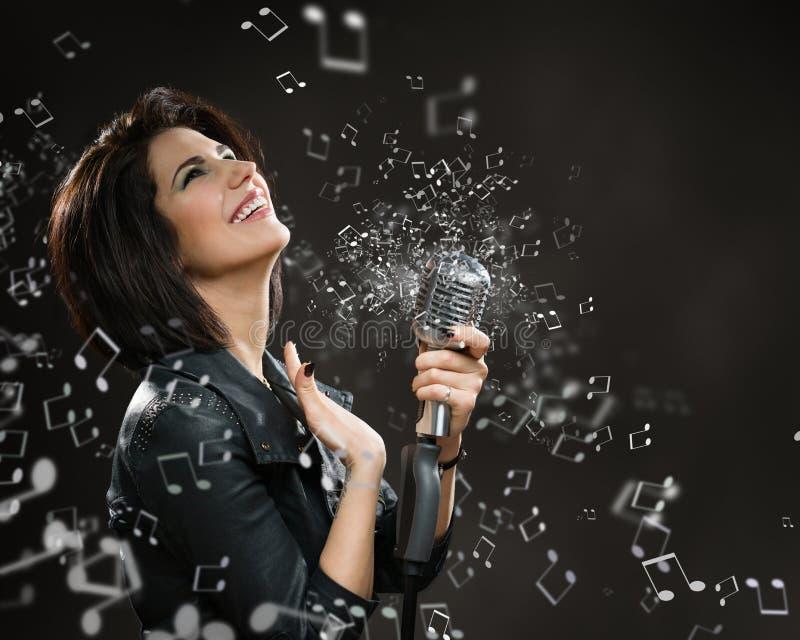 Musicista femminile della roccia che passa suonando mic fotografia stock libera da diritti