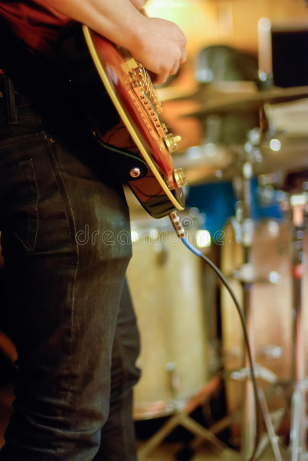 Musicista Playing Guitar in una banda del garage fotografia stock libera da diritti