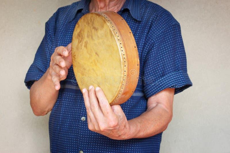 Musicista senior che gioca tamburo etnico. fotografia stock
