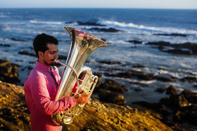 Musicista solo che gioca la tuba sulla costa dell'oceano immagini stock libere da diritti
