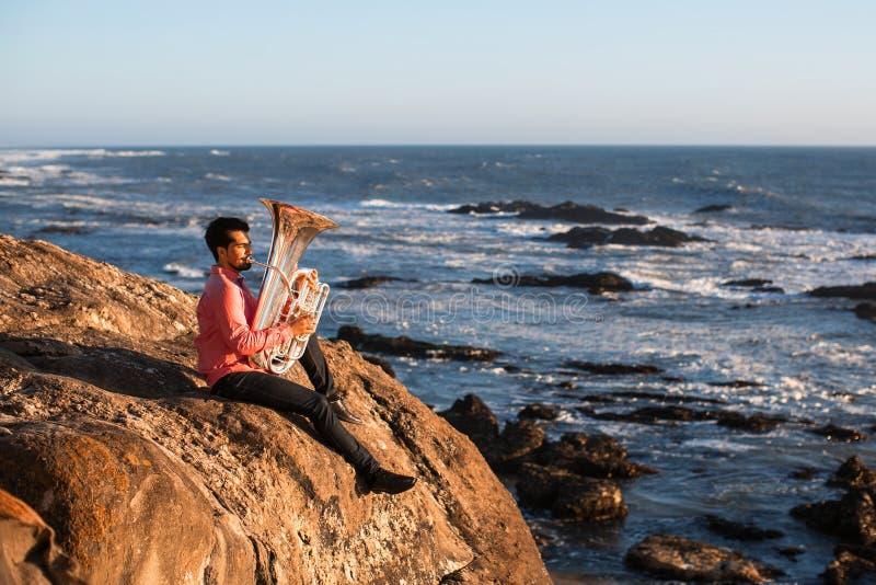 Musicista solo che gioca la tuba sulla costa di mare fotografia stock