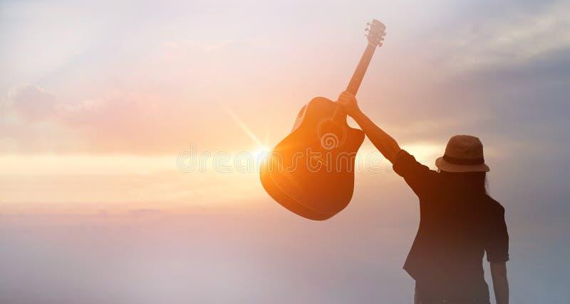Musicus die akoestische gitaar houden van silhouet op zonsondergang in hand stock afbeeldingen