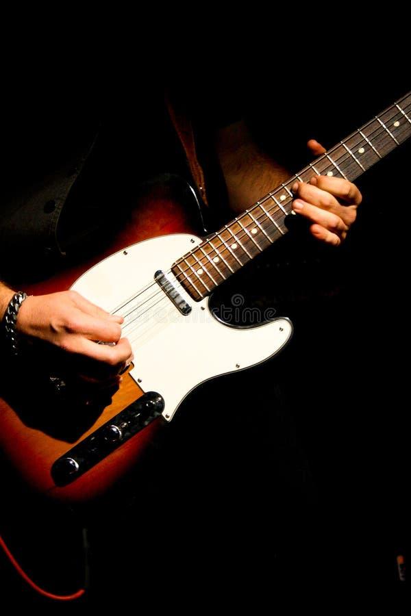 Musicus die de gitaar in een overleg spelen stock foto's
