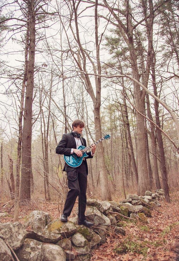 Musicus die gitaar speelt in het bos royalty-vrije stock afbeeldingen