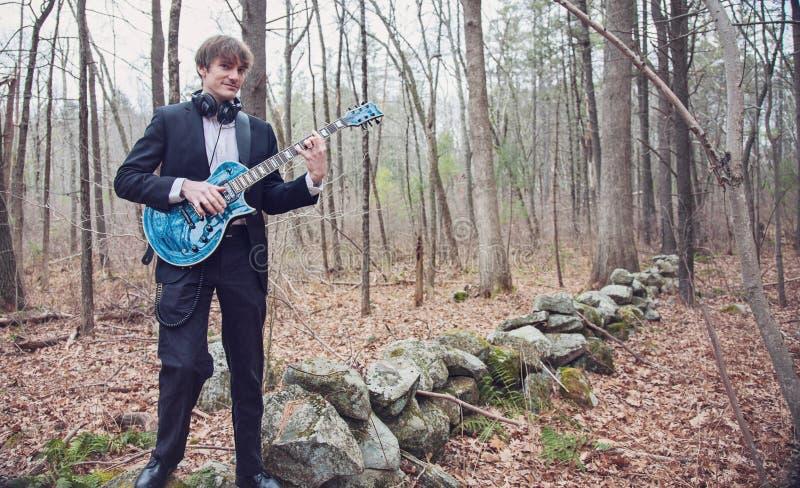 Musicus die gitaar speelt in het bos stock foto