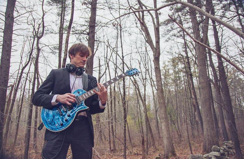 Musicus die gitaar speelt in het bos stock foto's