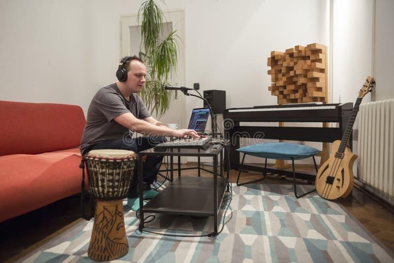Musicus die het toetsenbord van Midi in de studio van de huismuziek spelen stock afbeeldingen