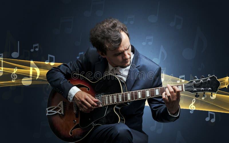 Musicus het spelen op gitaar met rond nota's royalty-vrije stock afbeeldingen