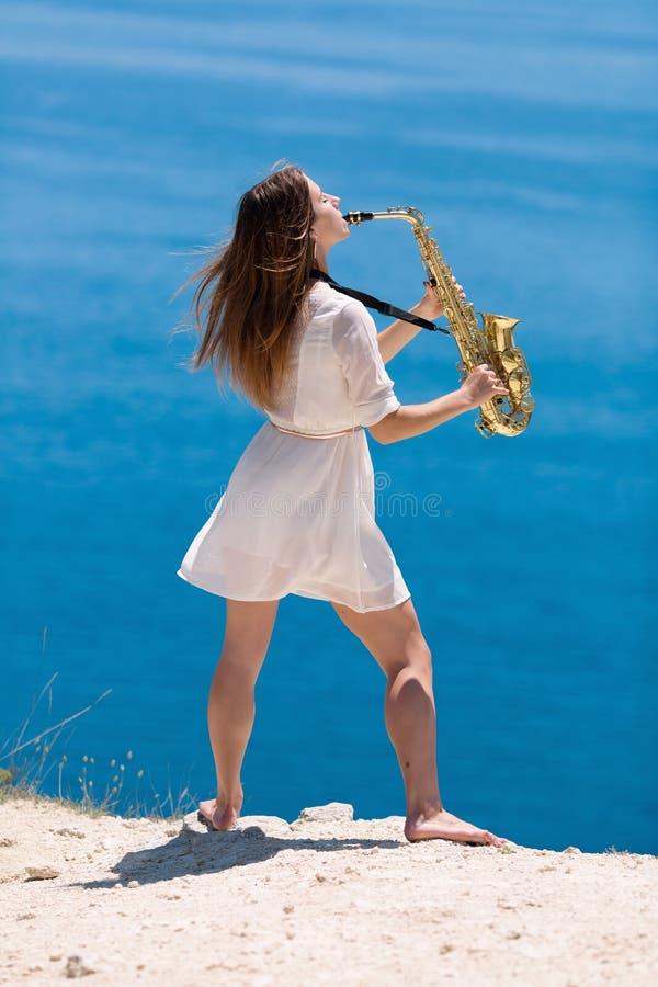 Musicus op rotsachtige kust stock foto's